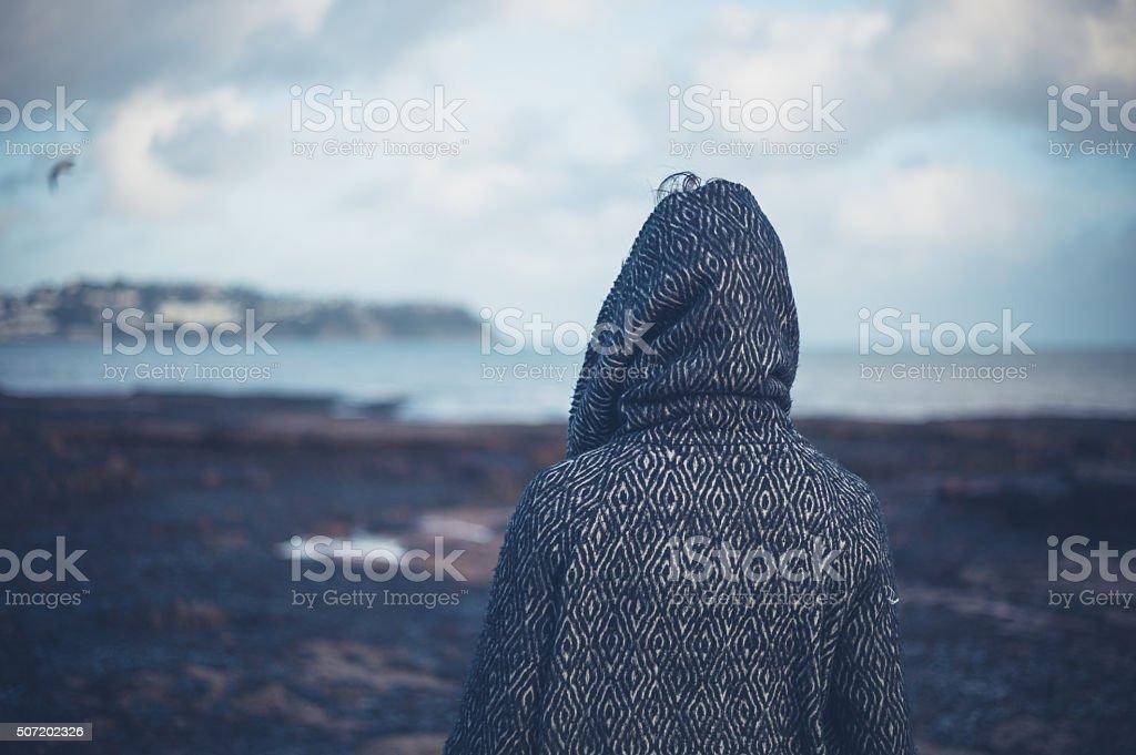 Junge Frau in Kapuzenmantel zu Fuß am Strand Lizenzfreies stock-foto