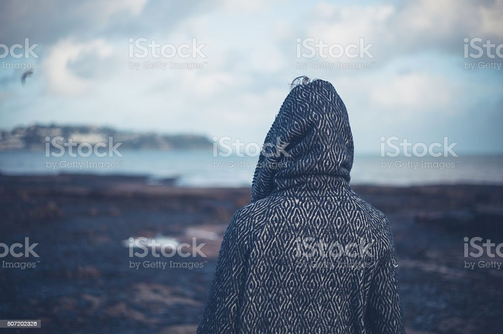 Young woman in hooded coat walking on beach stock photo