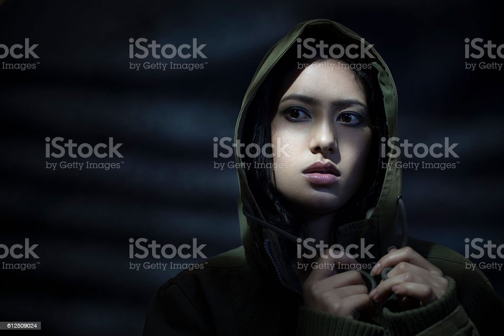 Young woman in hoodie under dark shadows looking away mysteriously. stock photo