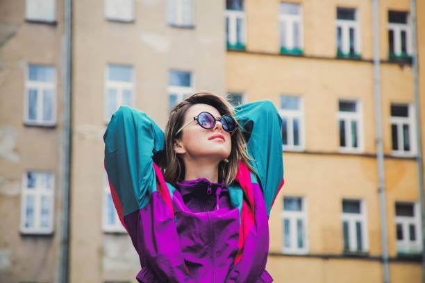 junge frau in jacke im 90er-jahre-stil bleiben im hinterhof - 80er outfit stock-fotos und bilder
