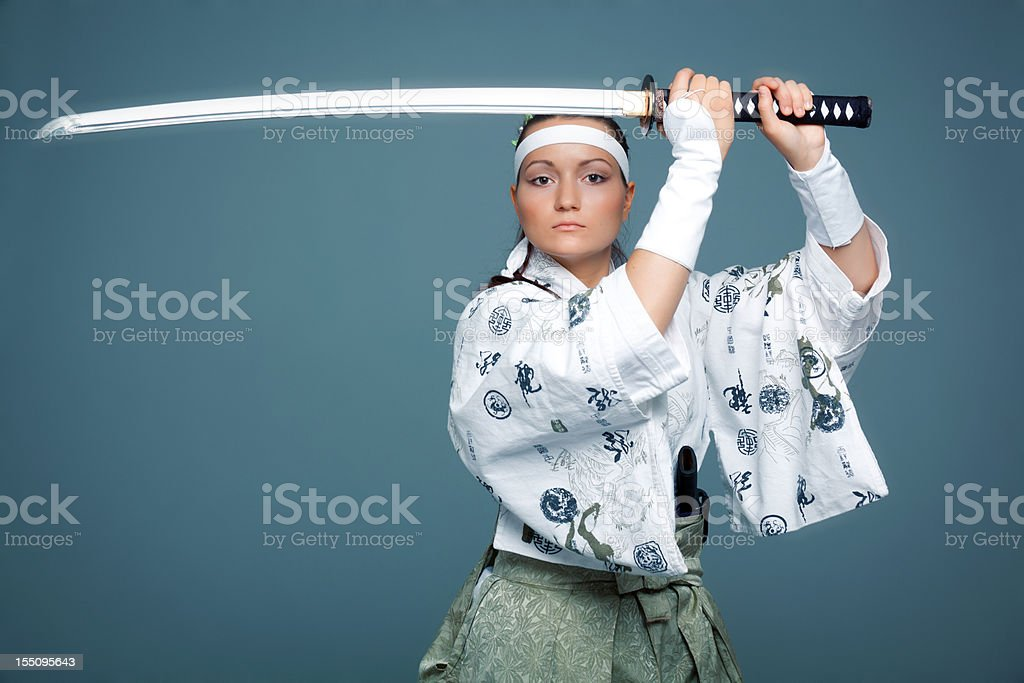 Young woman in japanese clothes defends herself with katana stock photo