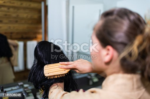 Young woman in kimono getting ready by traditional room brushing holding black wig in Japanese house home