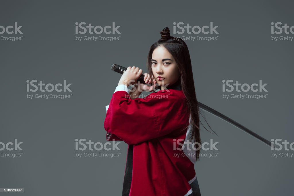 mujer en kimono manteniendo katana y mirando a cámara aislada en gris foto  de stock libre ca55f9949944