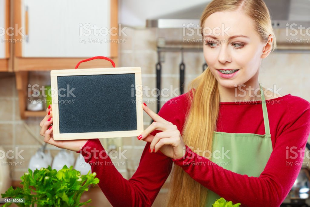 Young woman in kitchen holding blank board foto de stock royalty-free