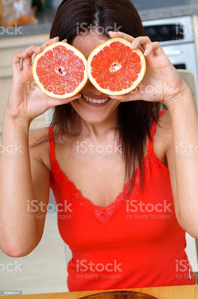 young woman in kitchen keeps Grapefruit royalty-free stock photo