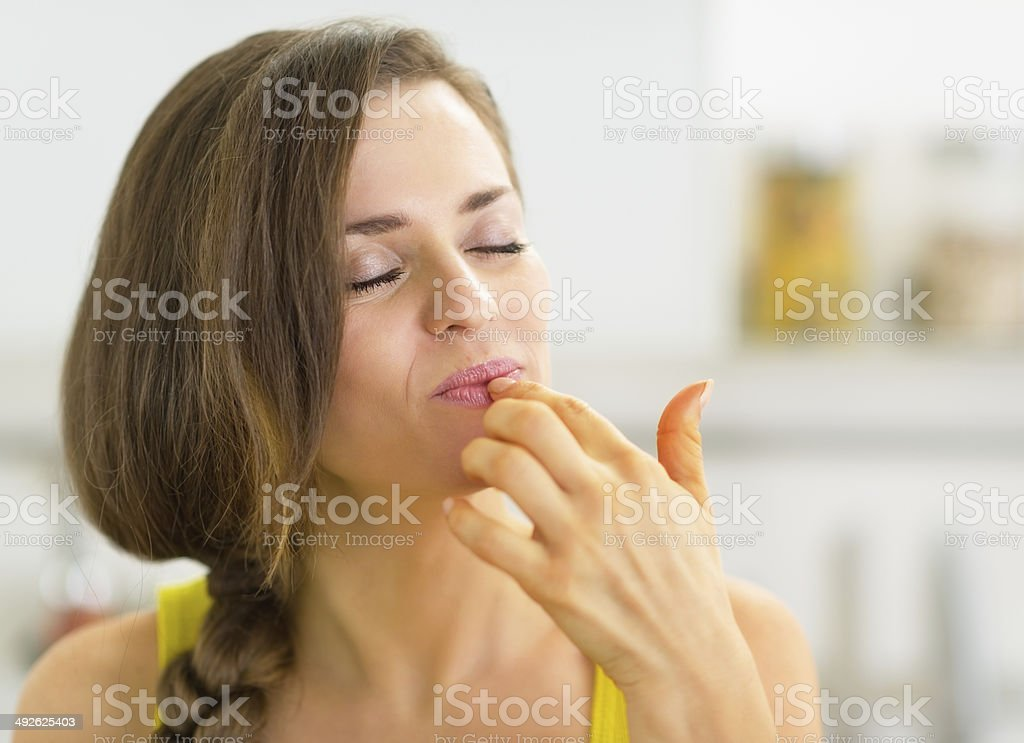 young woman in kitchen licking fingers stock photo