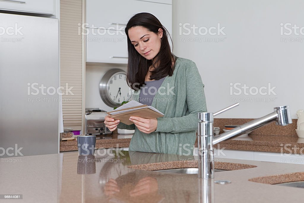 Young woman in kitchen looking at mail stock photo