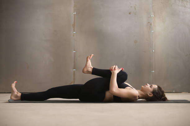 Young woman in Knees to Chest, Apanasana pose, grey studio Young attractive sporty woman practicing yoga, stretching in Knees to Chest, Apanasana exercise, working out, wearing black sportswear, cool urban style, grey studio background, full length, side view apanasana stock pictures, royalty-free photos & images