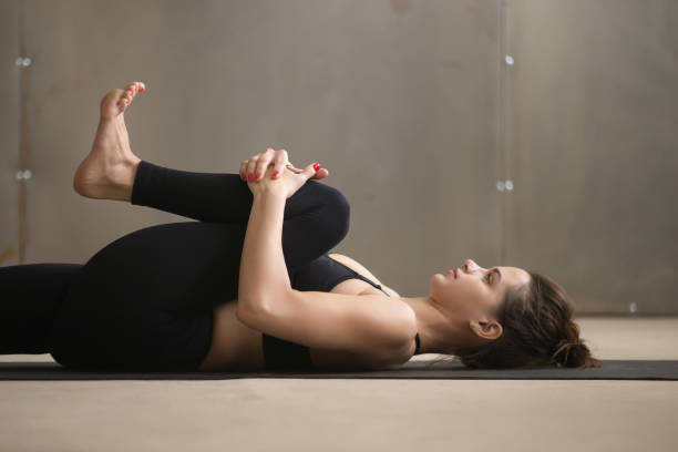 Young woman in Knees to Chest, Apanasana pose, studio, closeup Young attractive sporty yogi woman practicing yoga, stretching in Knees to Chest, Apanasana exercise, working out wearing black sportswear, cool urban style, grey studio background, closeup, side view apanasana stock pictures, royalty-free photos & images