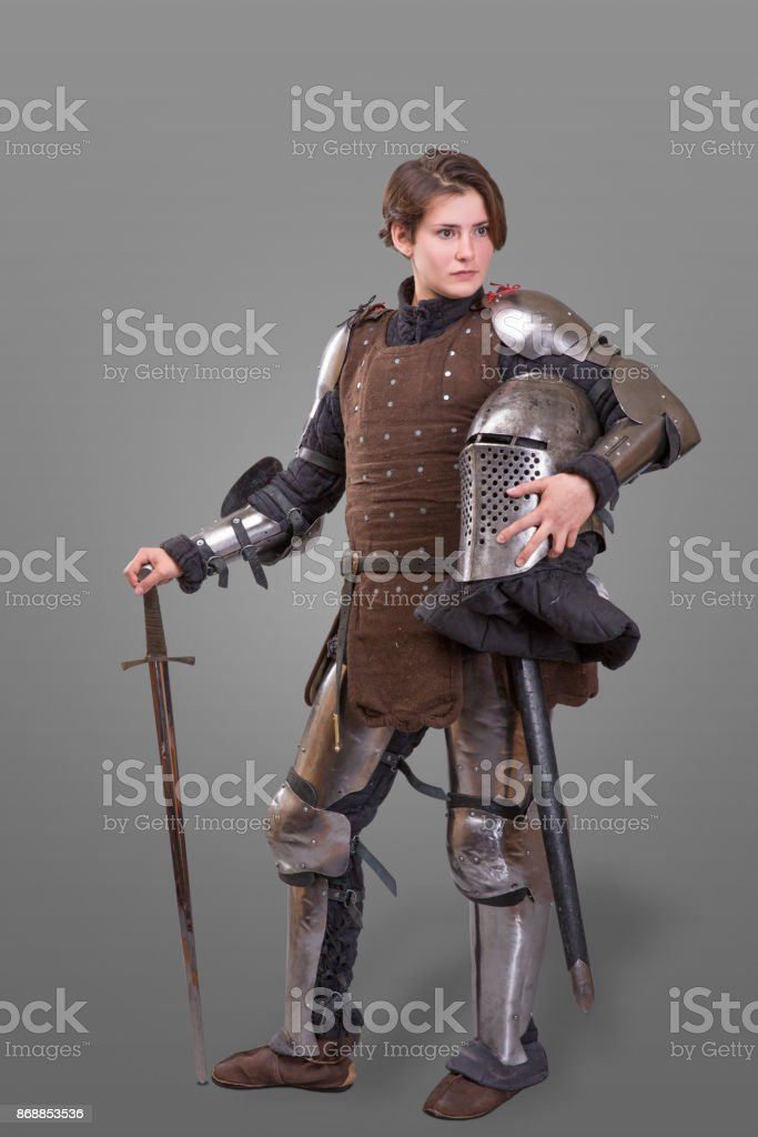 young woman in Knight Armour holding helmet in one hand and sword on her shoulder over grey background stock photo