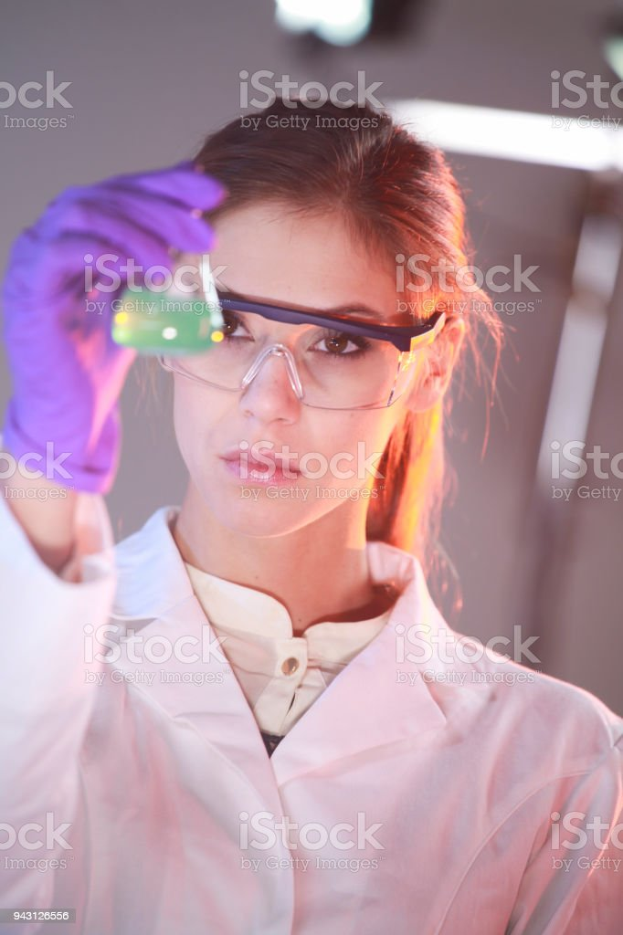 Young woman in lab looking at green sample stock photo