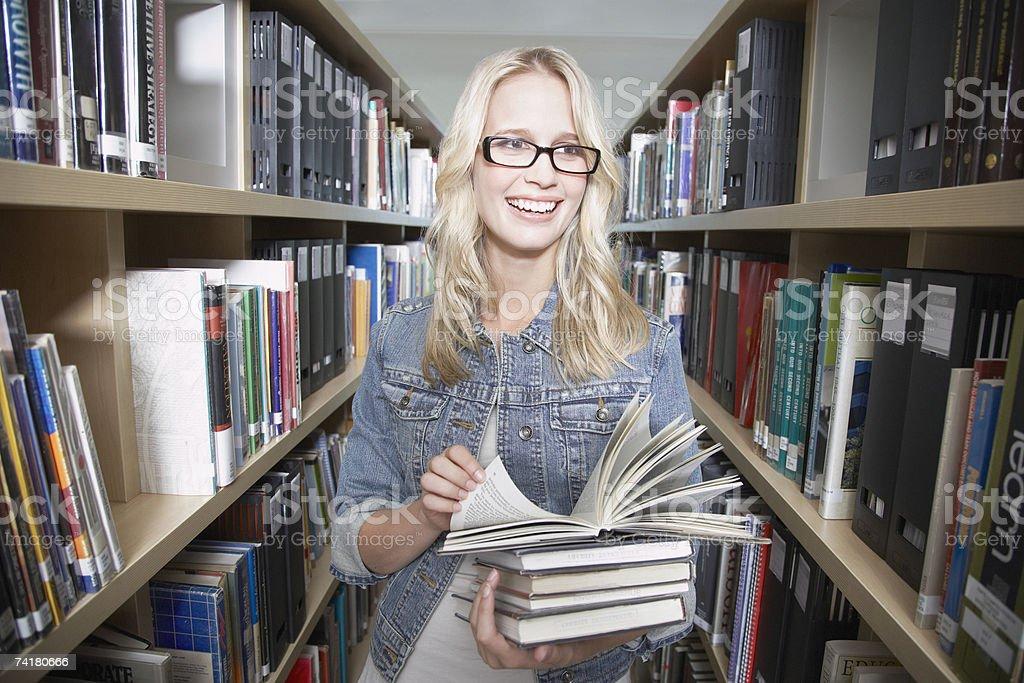 Jovem mulher na biblioteca na escola com Livros foto de stock royalty-free