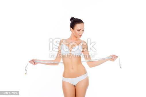 1163494373 istock photo Young woman in lingerie measuring her waist on white background 956397582