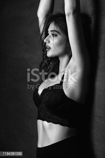 Sensual young woman leaning on the wall. She wearing black underwear and looks beautiful. Black and white photo