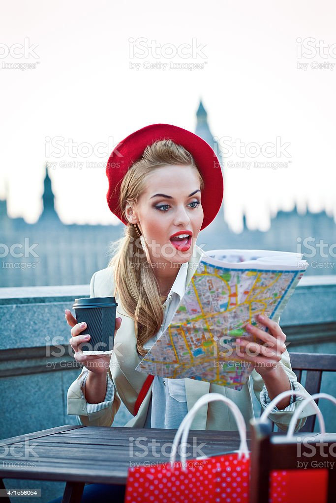 Young woman in London at sunset watching map stock photo