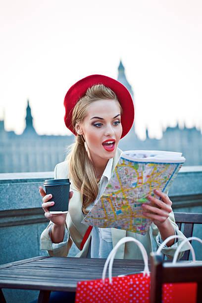 jeune femme dans la ville de londres au coucher du soleil en regardant la carte - mode londres photos et images de collection