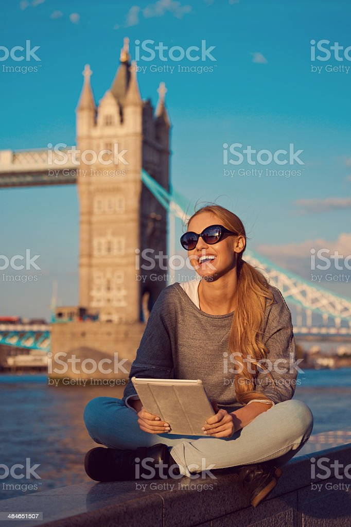 Young woman in London Outdoor portrait of happy young women using a digital tablet with Tower Brigde in the background. 20-24 Years Stock Photo
