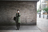 Vintage toned portrait of a young woman, wearing an olive green parka jacket, enjoying a beautiful day in London, taking photos with her analog film camera. Casual look, street style fashioned portrait in UK capitol.