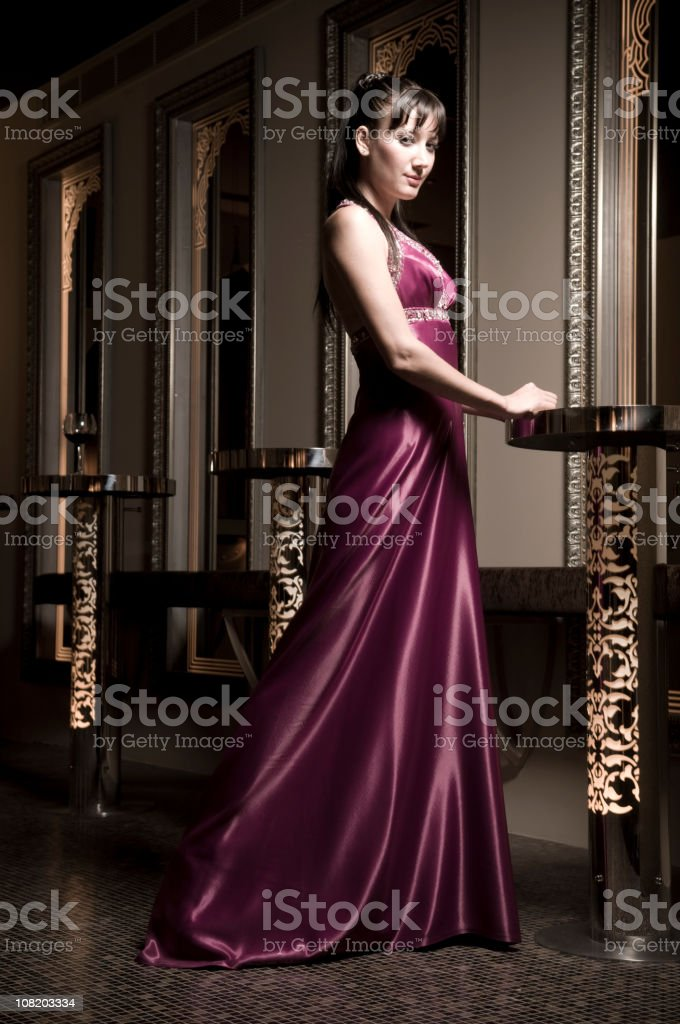 Young Woman in Long Dress Resting Hands on Nightclub Table stock photo