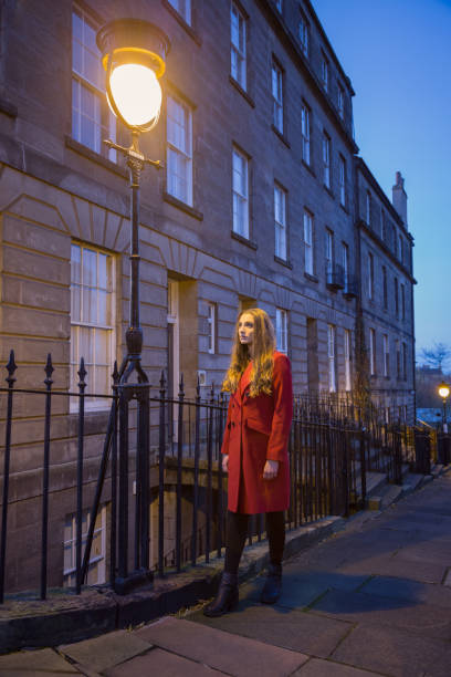 Young woman in long red coat under an old streetlight stock photo