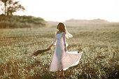 トウモロコシ畑の長い白いレースのドレスの若い女性。