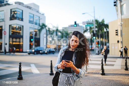 istock Young woman in Los Angeles, trying to find a rideshare service 1146051058