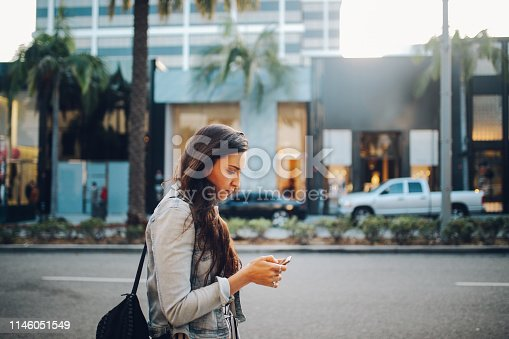 istock Young woman in Los Angeles, trying to find a rideshare service 1146051549
