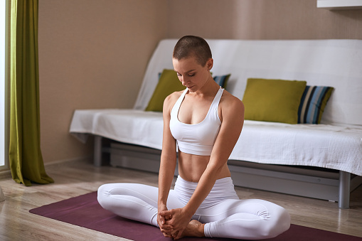 1071305850 istock photo Young woman in lotus pose, background room at home 1239157670