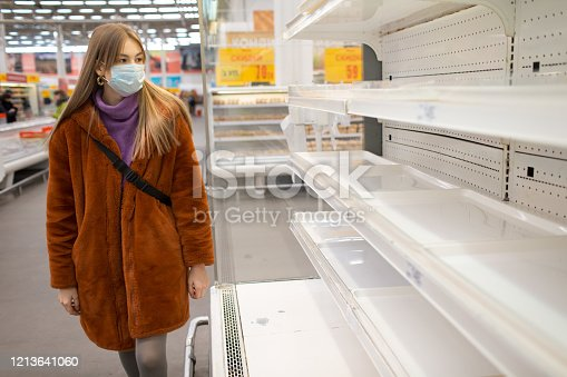 Young woman in medical mask and empty shelves in supermarket