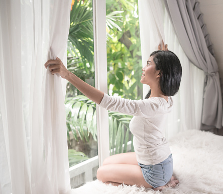 680846060 istock photo young woman in modern house opening window curtains after wake up 943697956
