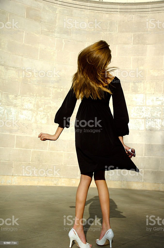 Young Woman in Motion Black Dress stock photo