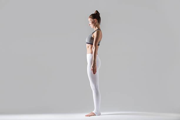 Young woman in mountain pose, grey studio background - foto de stock