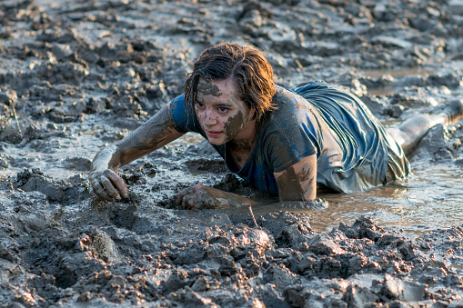 687723318 istock photo Young Woman in Mud Run 687723296