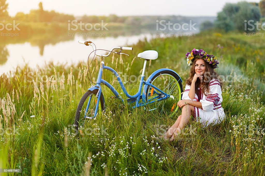Young woman in national ukrainian folk costume with bicycle stock photo