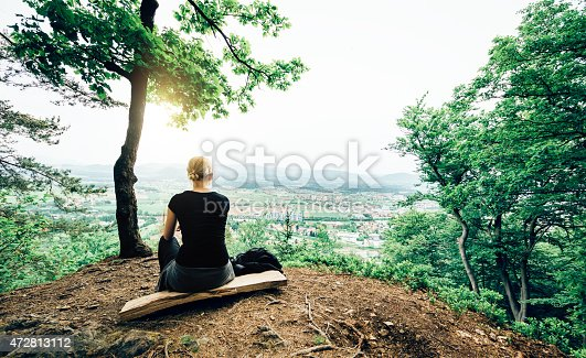 Young woman sitting on a bench on the top of a hill looking down on her home town.