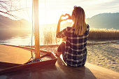 Young woman sitting on a boat bow by the lake making a heart shape with her hands. Lake and mountain as a landscape. Swiss Alps on the background.