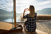 istock Young woman in nature making heart shape finger frame 640056628
