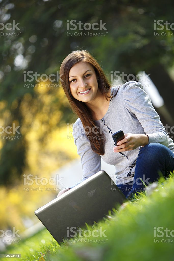 Young woman in nature using cell phone royalty-free stock photo