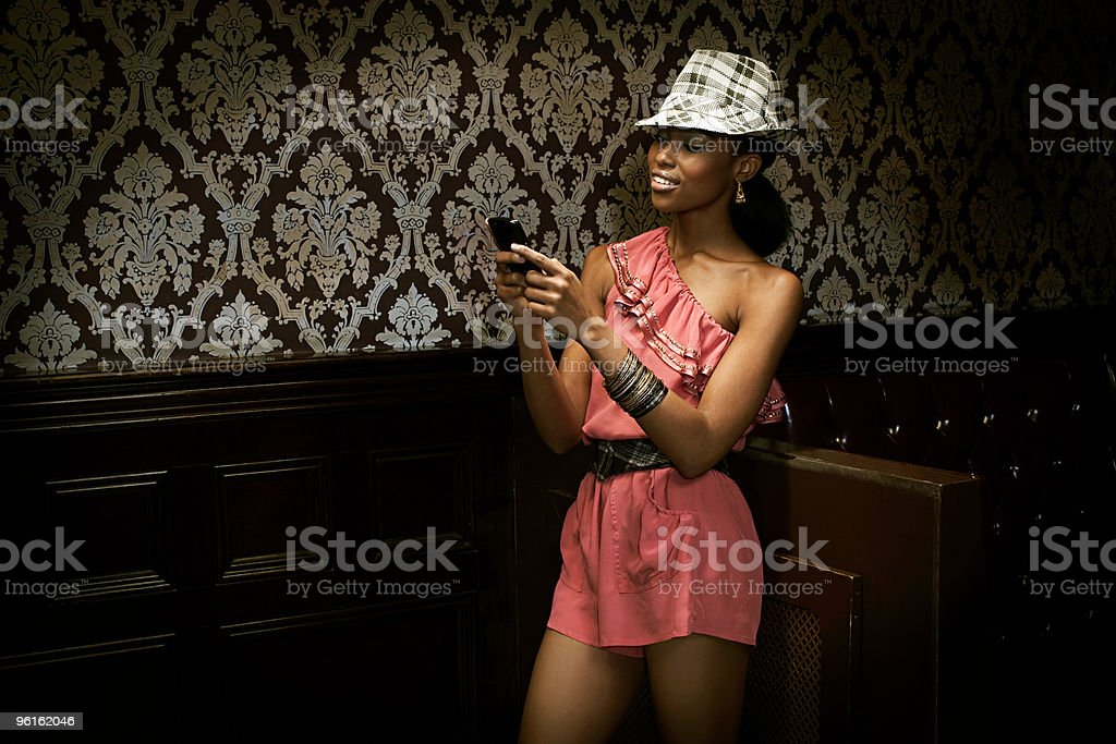 Young woman in nightclub with cellphone stock photo