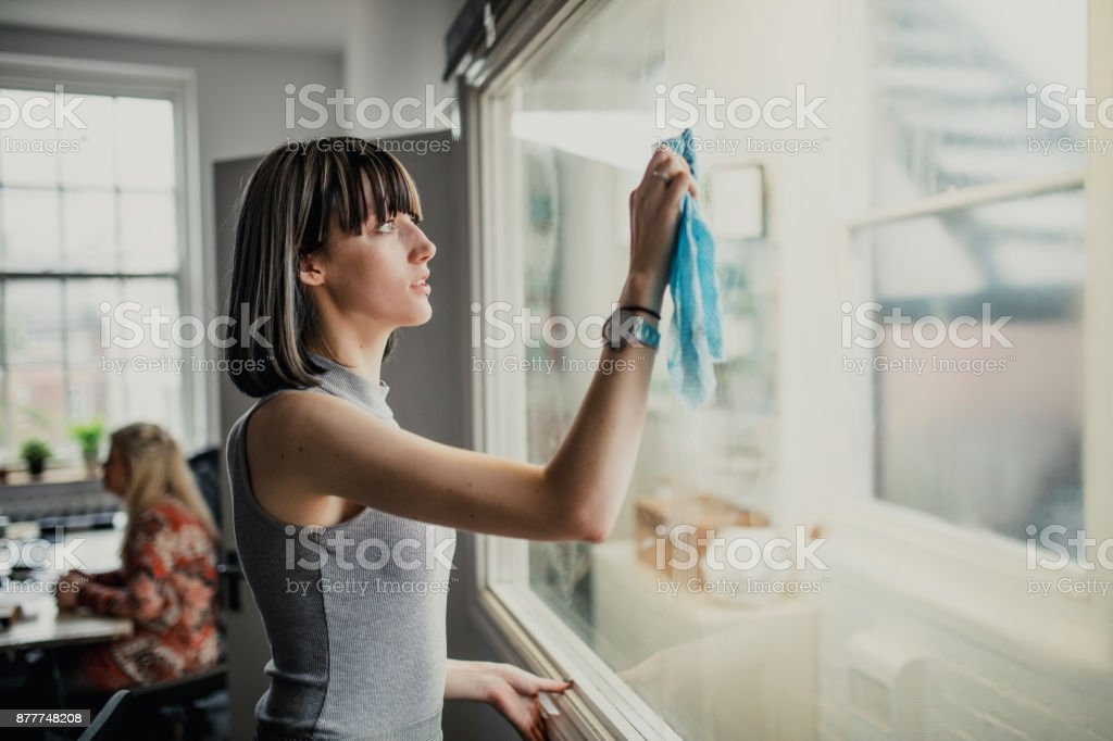 Young Woman in Office Cleaning stock photo