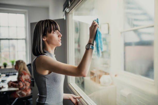 young woman in office cleaning - day in the life series stock pictures, royalty-free photos & images