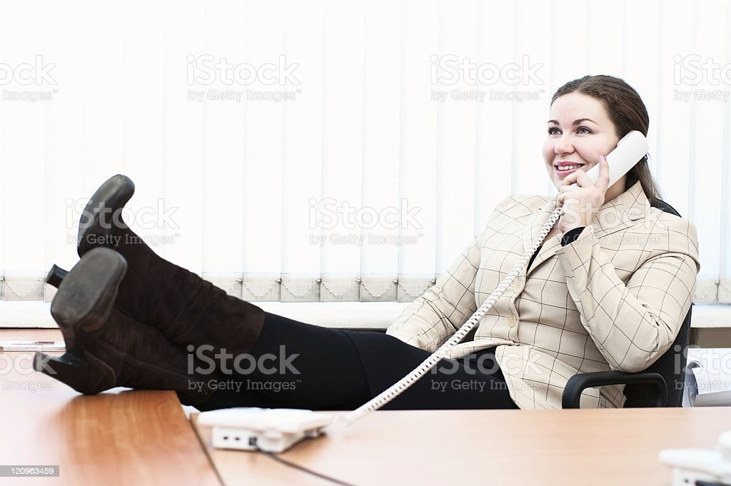Young woman in office interior calling by telephone royalty-free stock photo