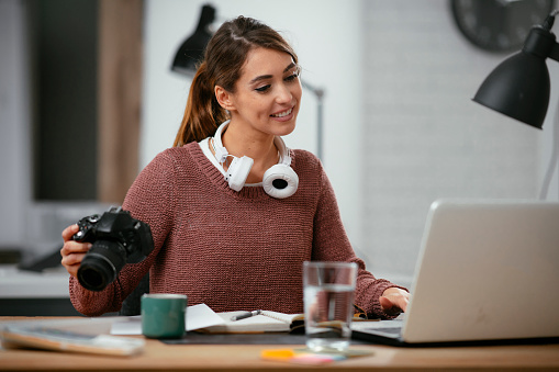 Young woman in office with camera