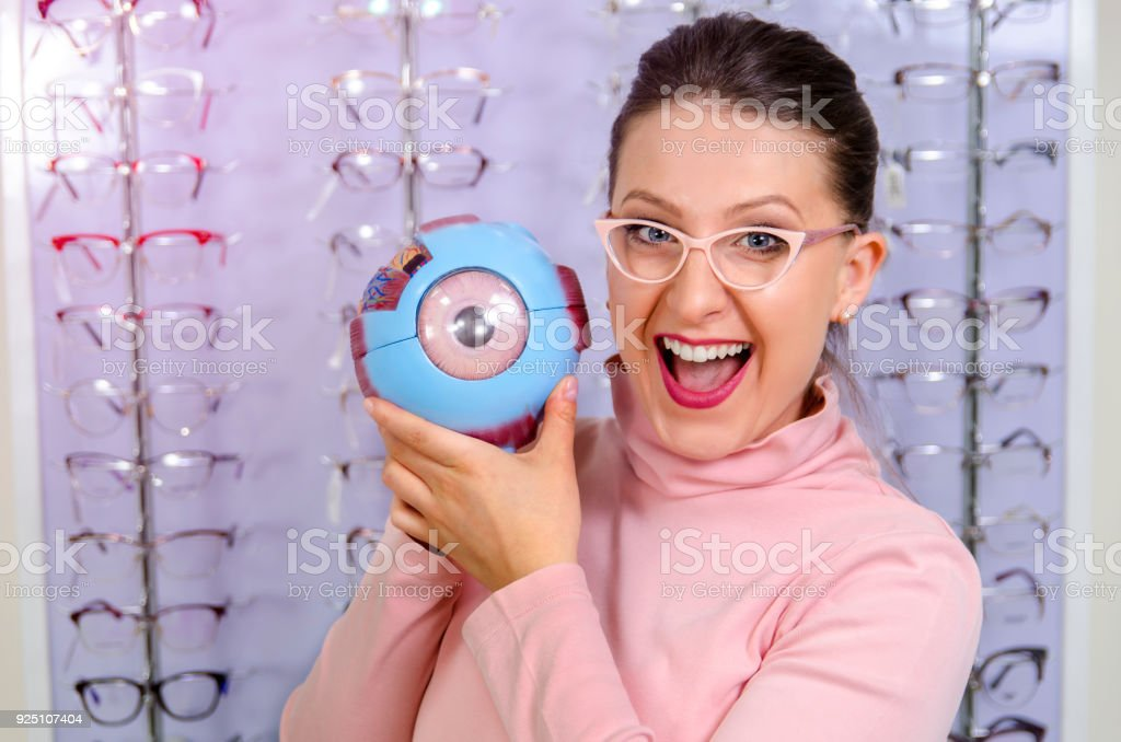 Young woman in optics store with plastic eye model stock photo