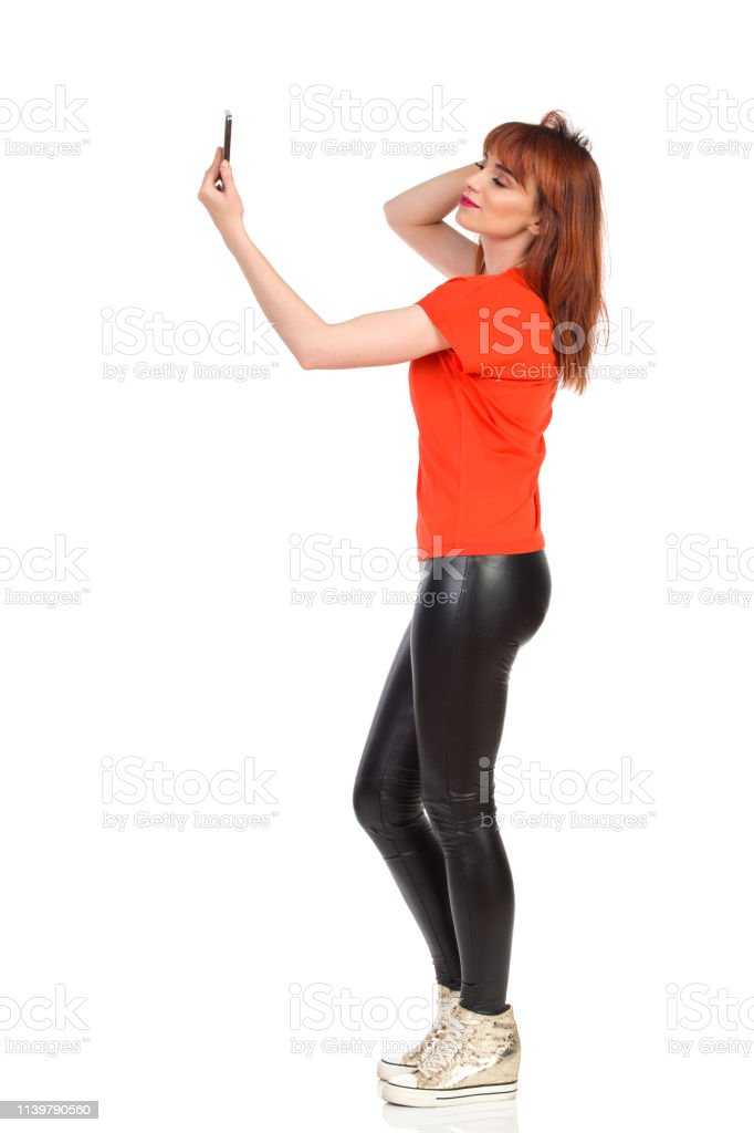 b8a886fb1d3ff2 Young Woman In Orange Shirt And Leggings Is Taking A Selfie royalty-free  stock photo
