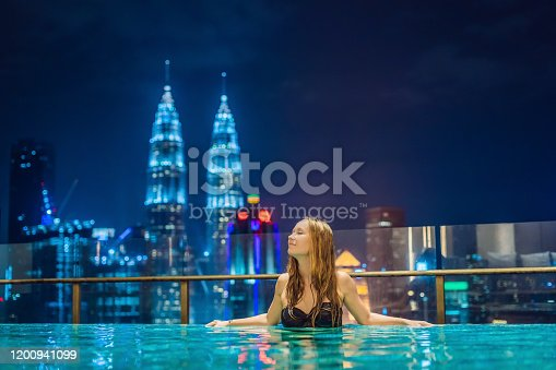 535761281 istock photo Young woman in outdoor swimming pool with city view at night 1200941099