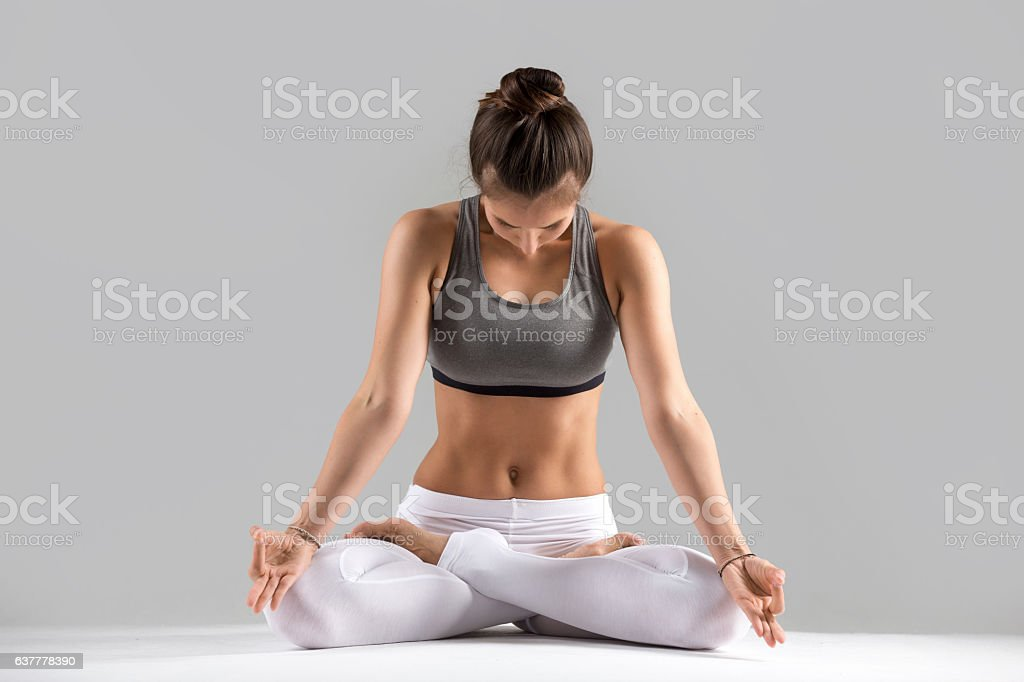 Young woman in Padmasana pose, grey studio background stock photo