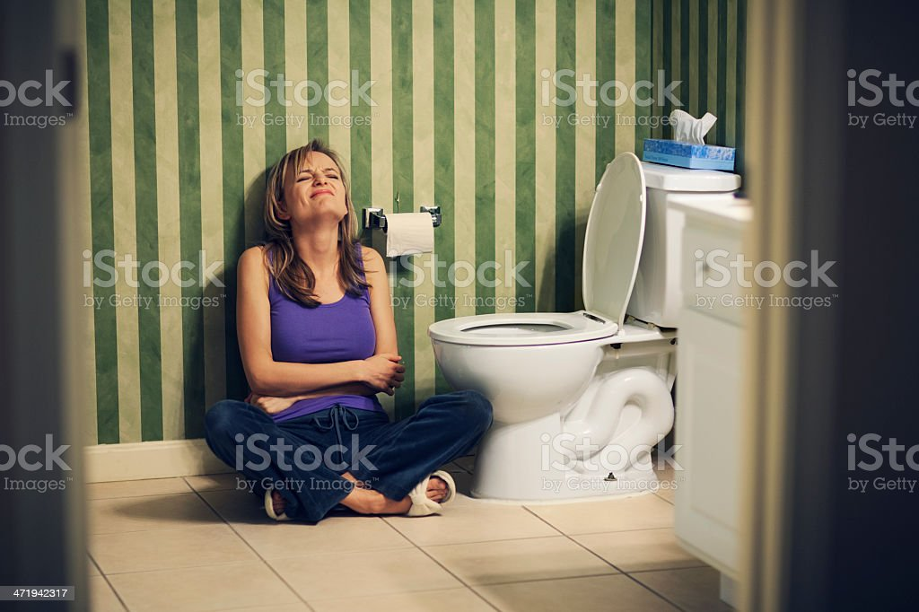 Young woman in pain on bathroom floor stock photo