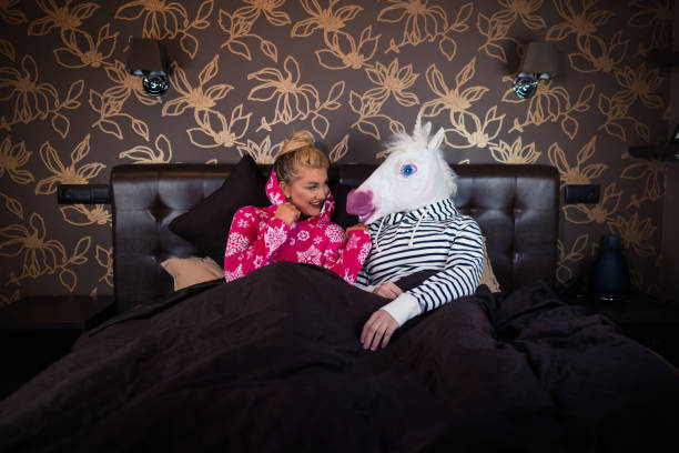 young woman in pajama sits on bed - unicorn bed imagens e fotografias de stock