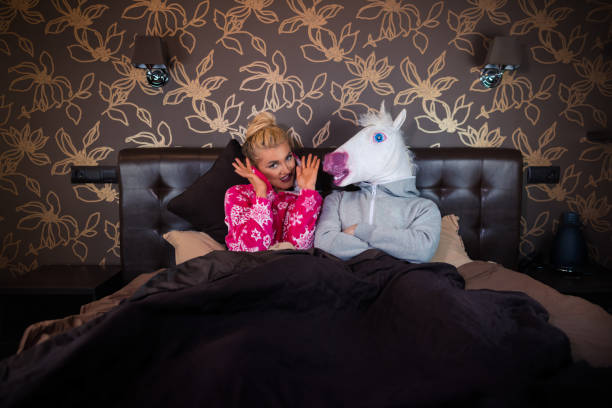 young woman in pajama sits on the bed - unicorn bed imagens e fotografias de stock